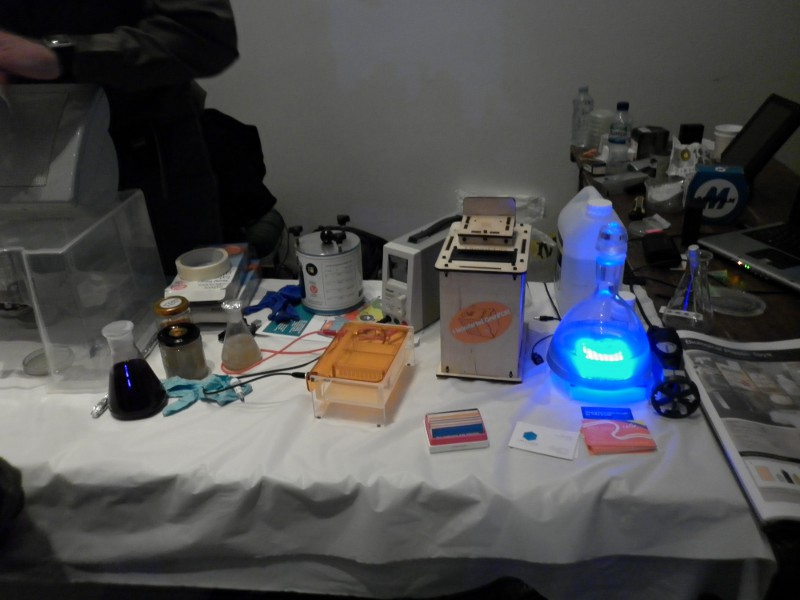 Our 2011 DIYbio table, complete with OpenPCR, Pearl Biotech Gel Electrophoresis Rig, NCBE and Dremelfuge Centrifuges, and more.